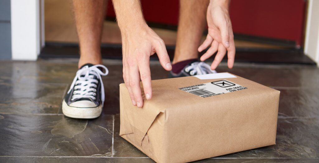 man picking up package outside of his home