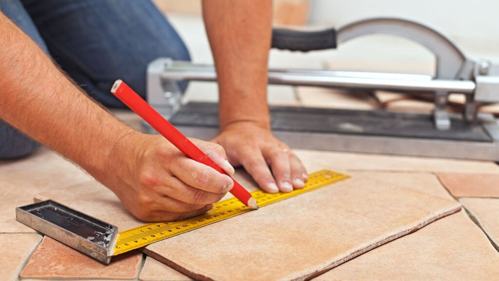 contractor making measurements on floor tile