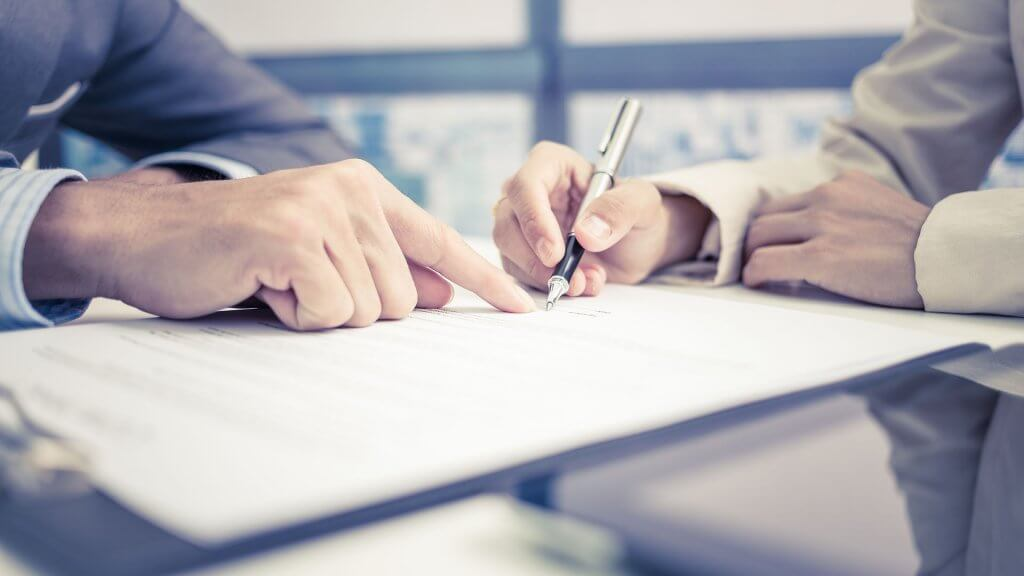 man pointing to where other man should sign on document