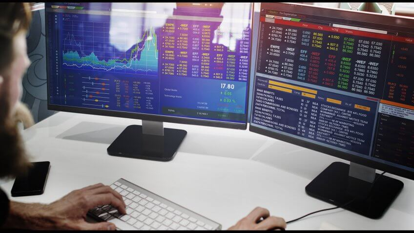 man checking stocks with two monitors