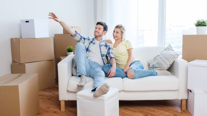 couple sitting on couch with moving boxes all around them