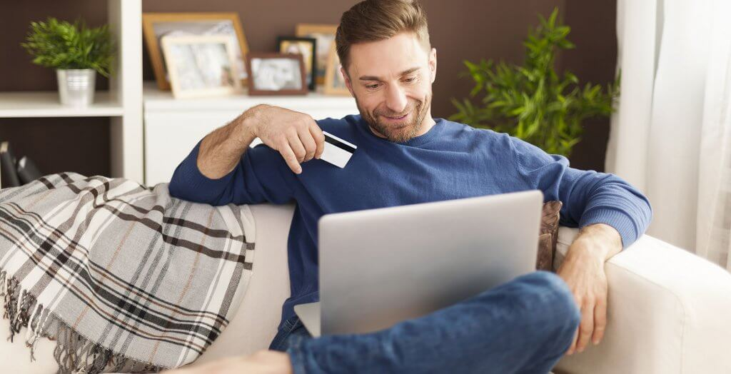man sitting on couch with laptop on his lap and holding a gift card or credit card