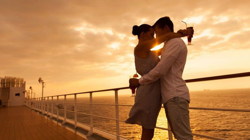 couple on cruise hugging with drinks at sunset