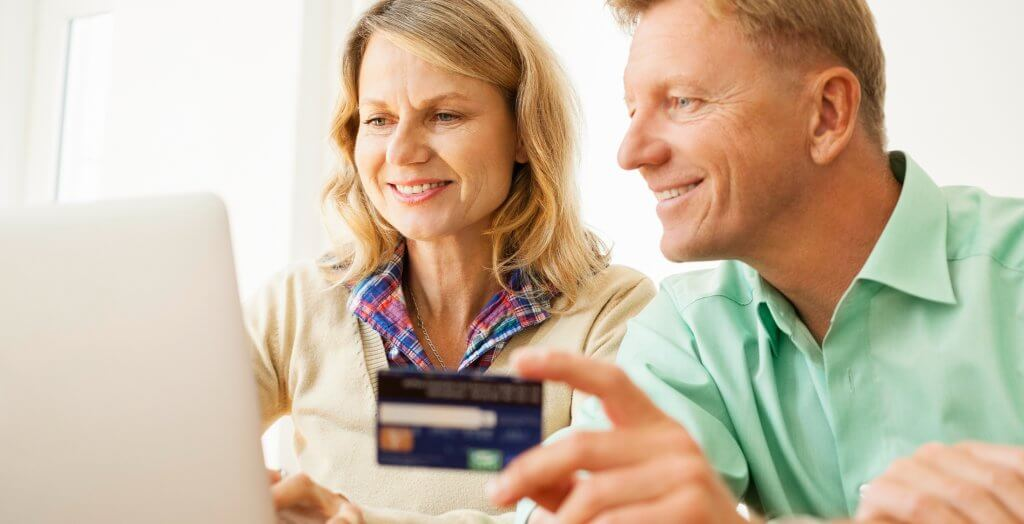 Happy mature couple sitting together at table using laptop and credit card for shopping online