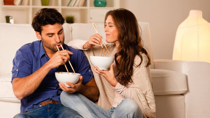 couple eating a bowl of food with chopsticks in their living room