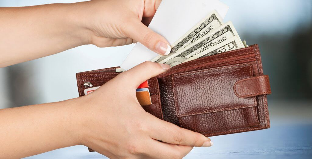 person holding wallet with cash and various cards
