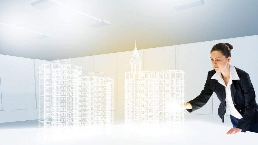 woman reaching out to holographic buildings