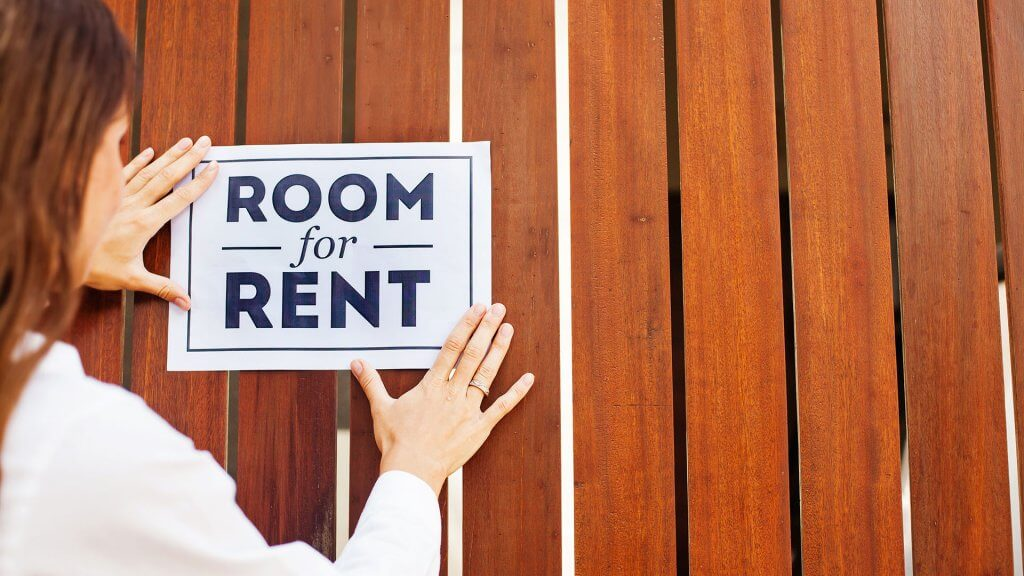 woman placing 'room for rent' sign up