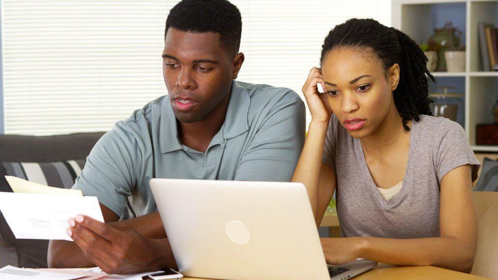 man and woman frustrated at computer and bills