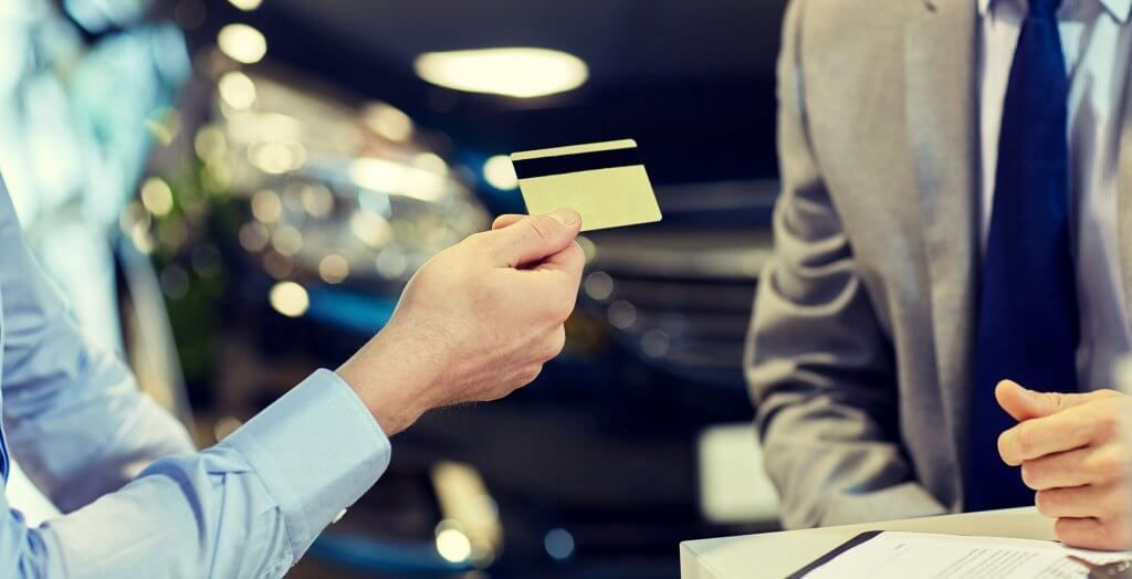 person handing credit to card to man