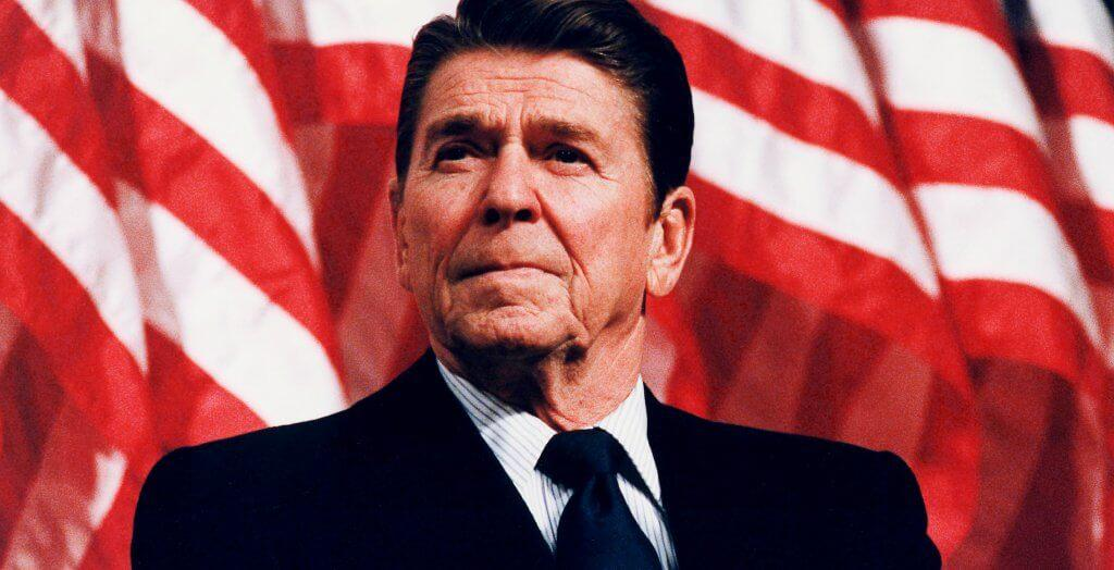 ronald reagan posing in front of the american flag