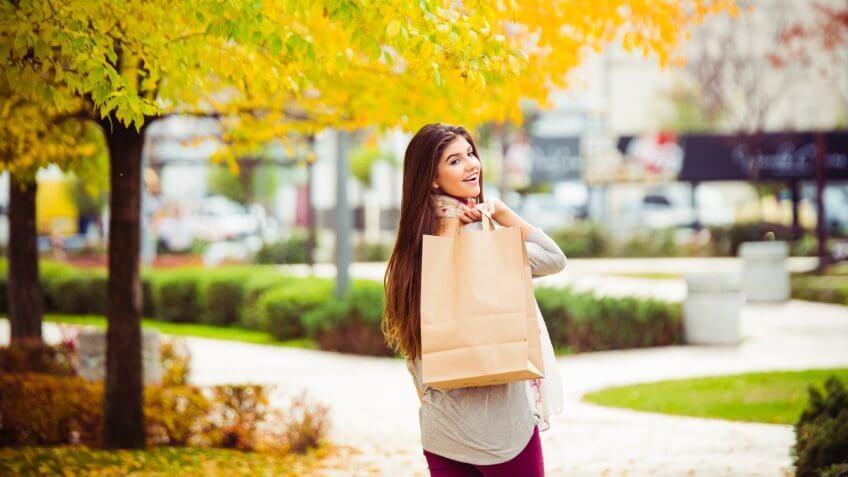 Shot of  young women walking down a street carrying shopping bags.
