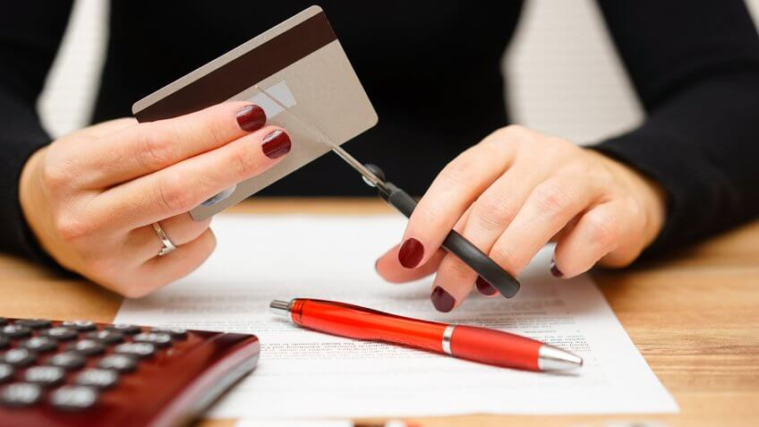 woman cutting up credit card