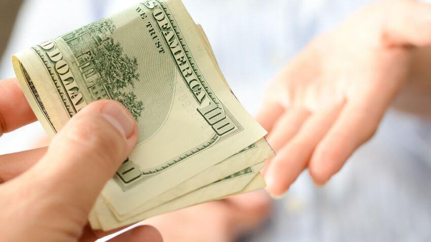 hands transferring $100 bills