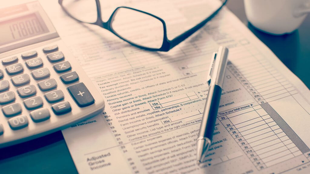 pen glasses and calculator on top of tax form