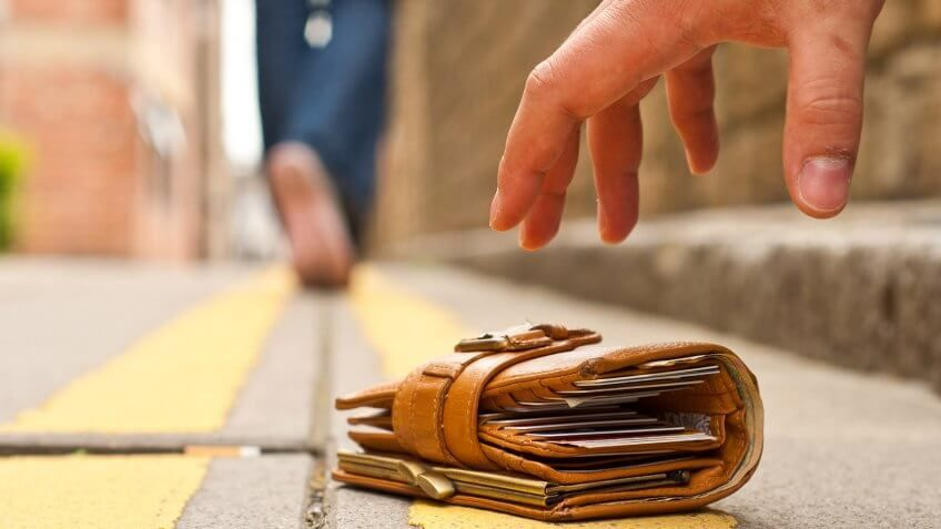 person reaching for wallet on the ground
