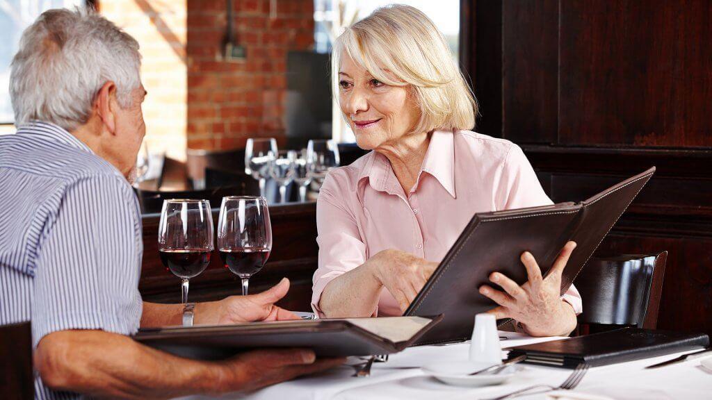 elderly couple ordering from menu at white linen restaurant