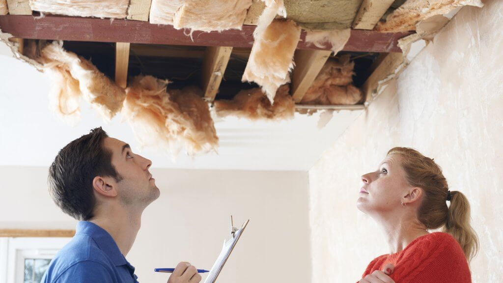 woman and contractor looking up at busted ceiling