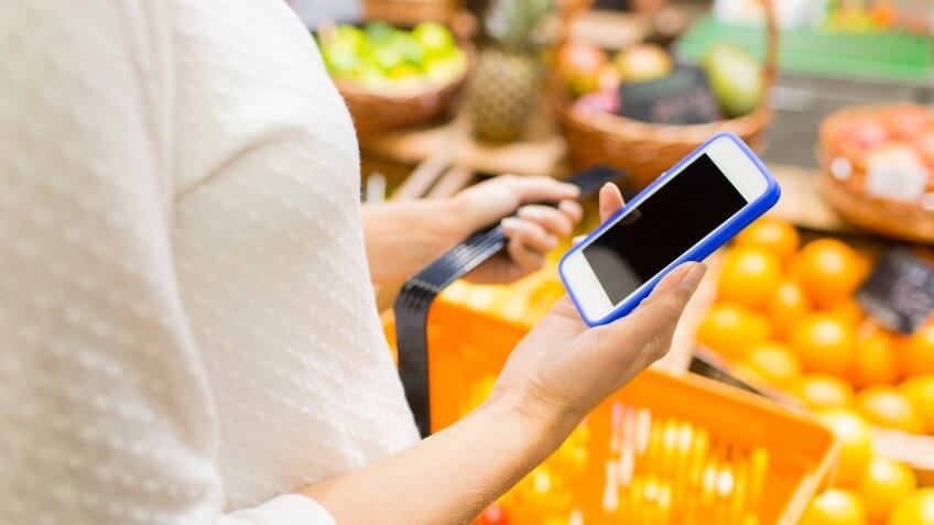 woman holding shopping basket and iphone