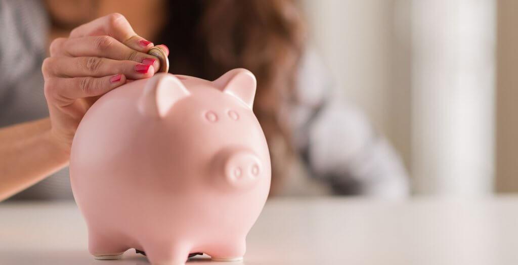 woman placing coin into piggy bank