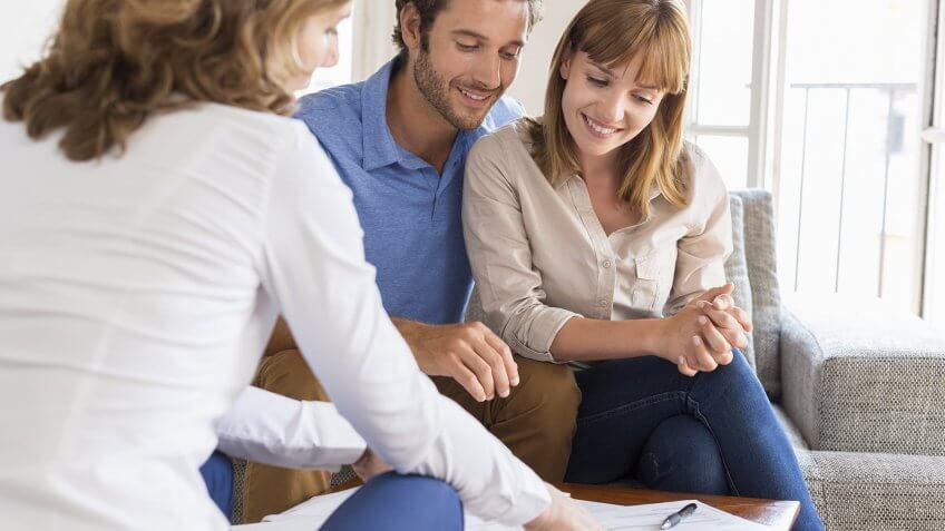 couple reviewing documents on table with third person