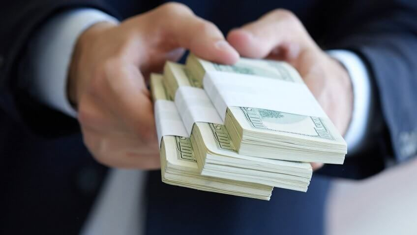 man holding stacks of $100 bills