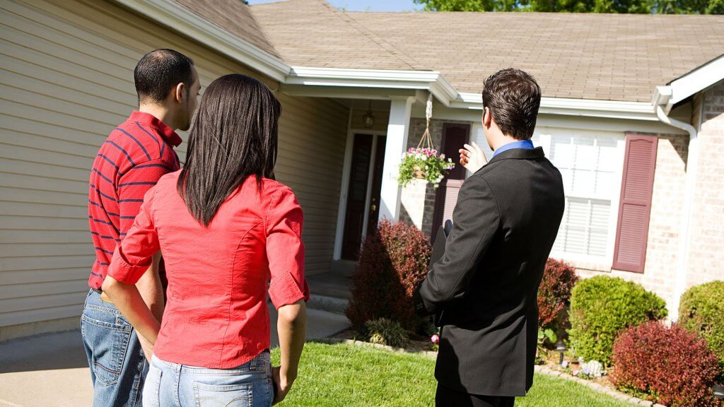 real estate agent showing couple exterior of house