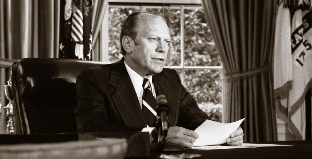 black and white photo of gerald ford sitting in the oval office