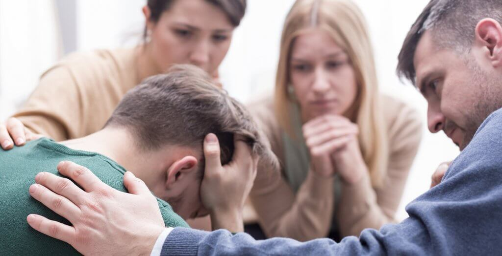 group trying to console upset man