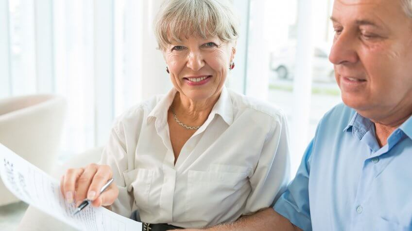 elderly couple looking over document