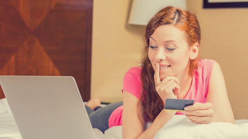 woman holding credit card and glancing at laptop