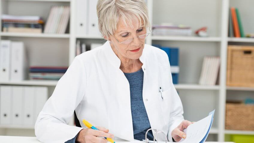 elderly woman in lab coat examining a document