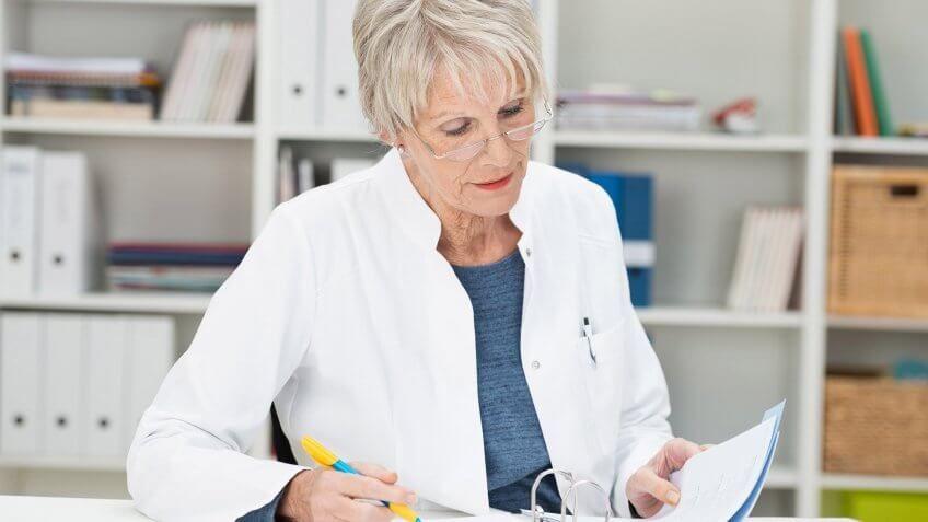 elderly woman in lab coat examining a document