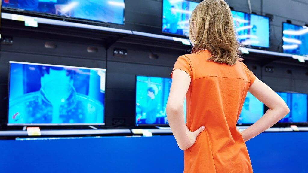 woman in orange dress shopping for TVs