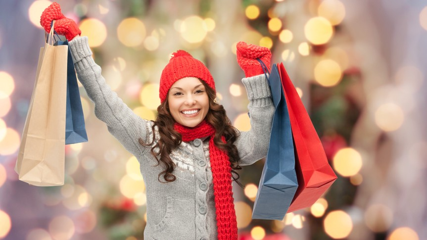 holidays, x-mas, sale and people concept - happy young asian woman in winter clothes with shopping bags over christmas tree lights background.