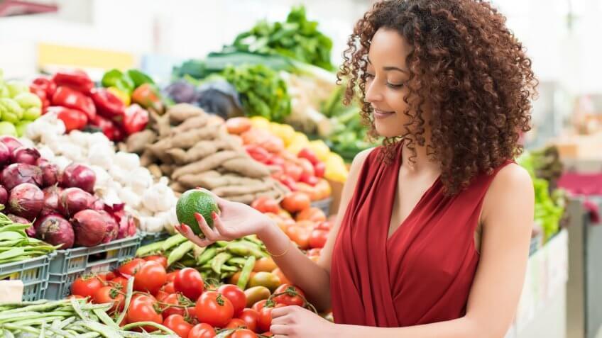 Afro woman shopping organic veggies and fruits.
