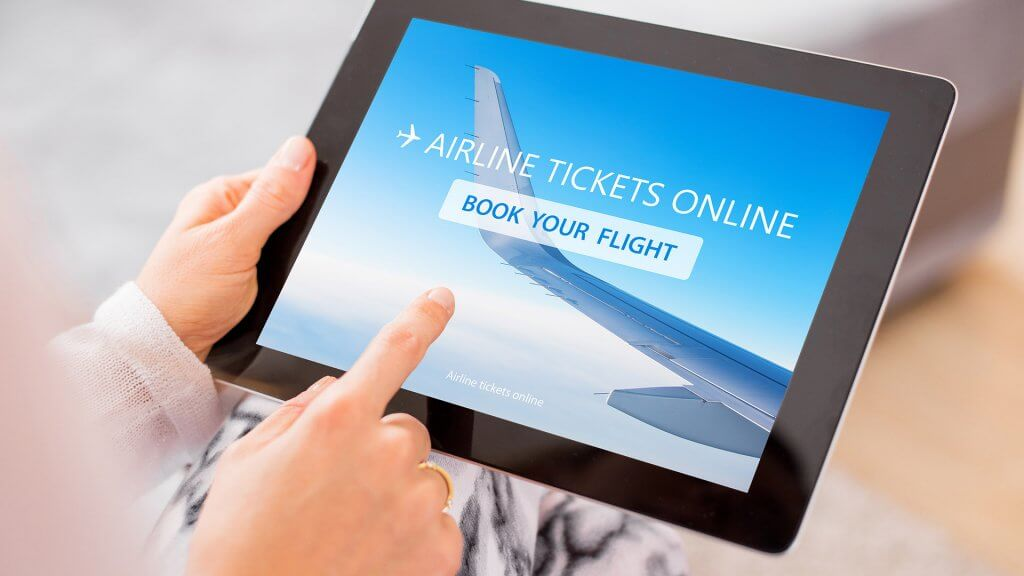hands using tablet to buy airplane tickets