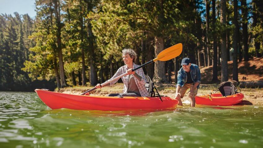 Senior couple having fun kayaking in the lake.