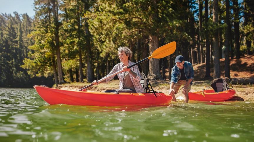 Senior couple having fun kayaking in the lake.