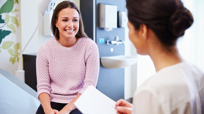 Female Patient And Doctor Have Consultation In Hospital Room.