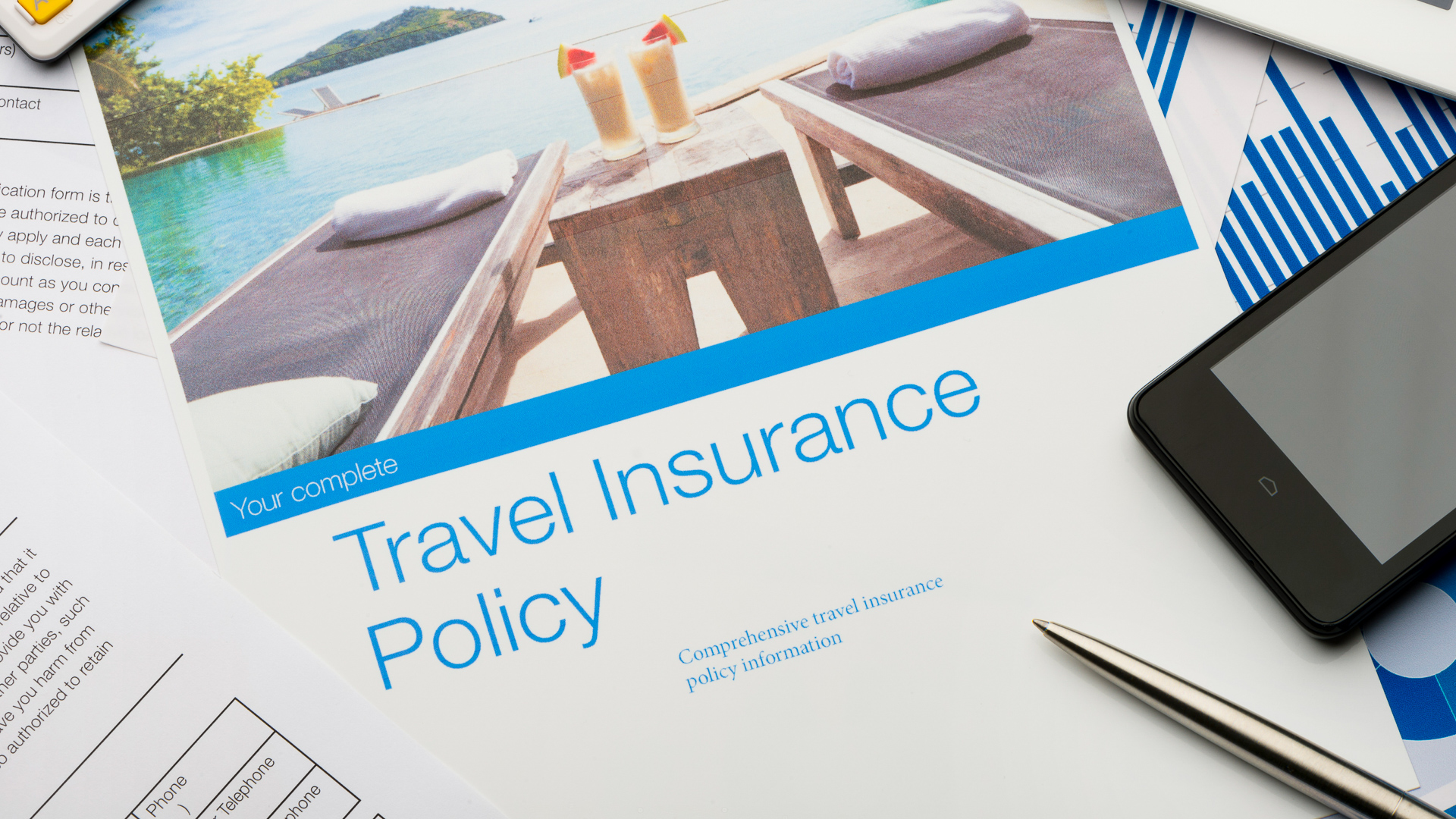 Travel insurance policy document with paperwork and technology.