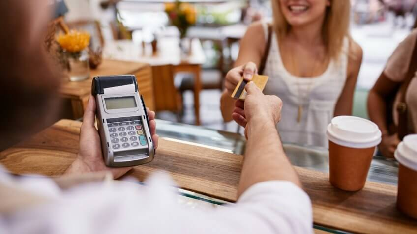 Customer paying for their order with a credit card in a cafe.