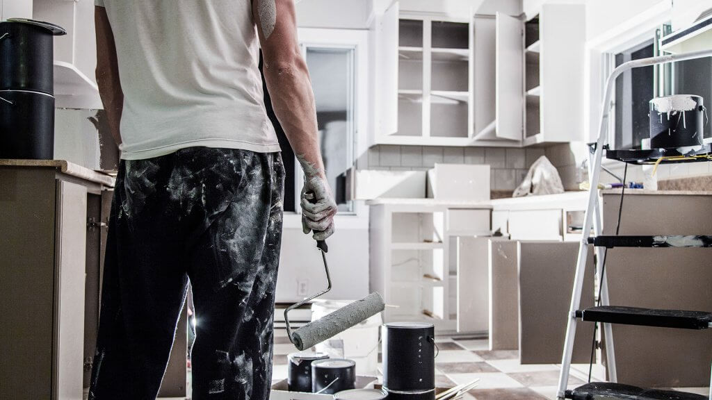 man covered in white paint painting kitchen white