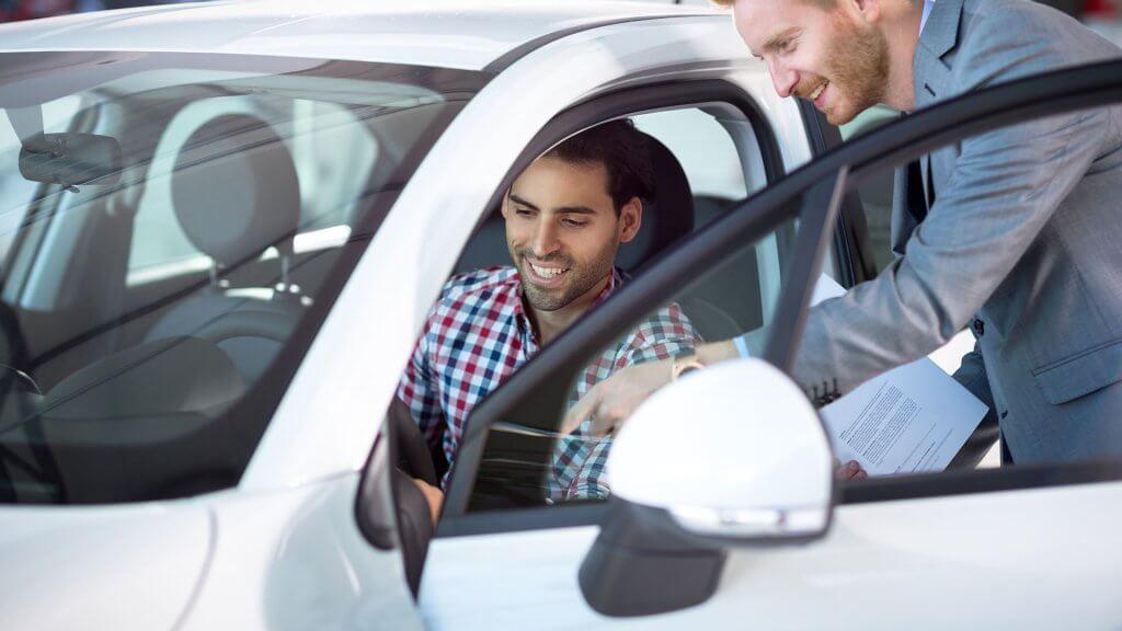 car salesman showing car to man