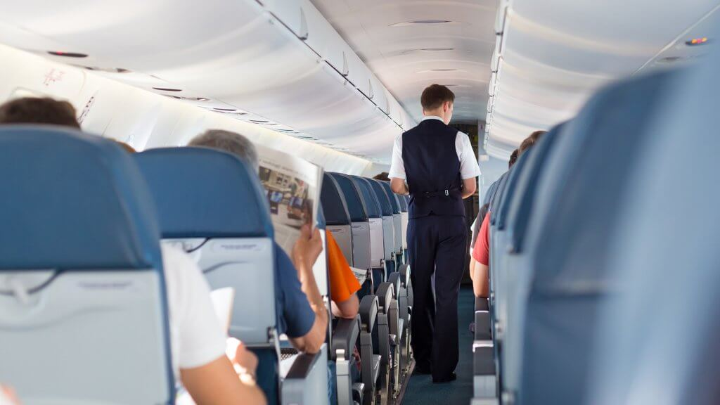 inside of plane with flight attendant walking down aisle