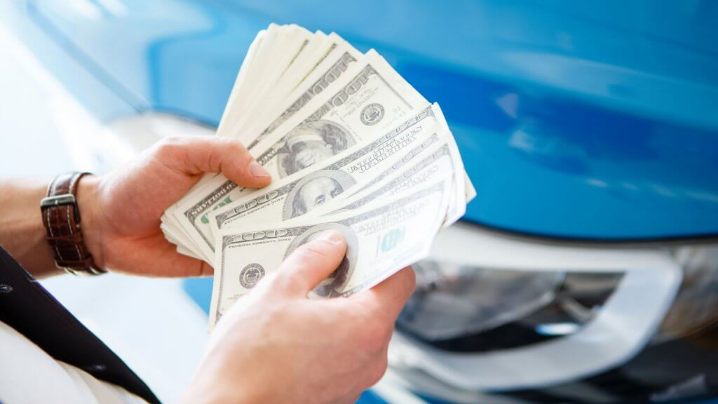hands counting $100 bills next to car