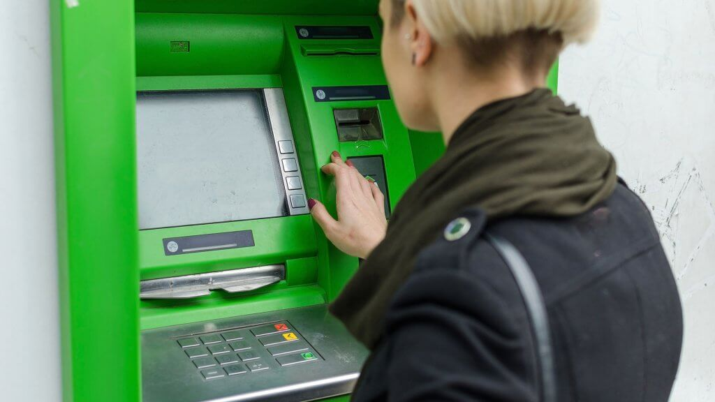 woman using green atm