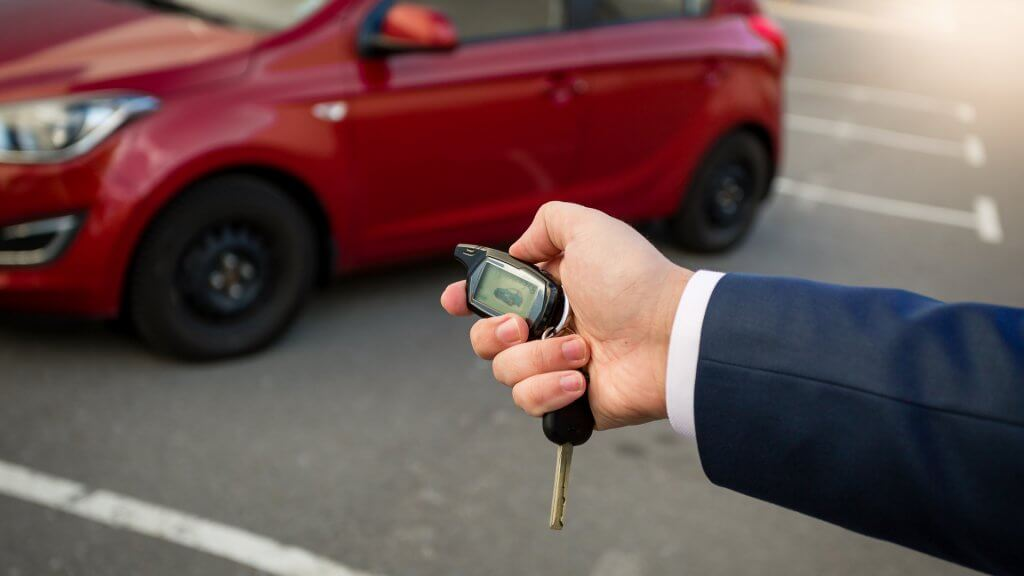 man pressing car alarm on key fob