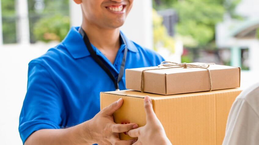 Woman hand accepting a delivery of boxes from deliveryman.
