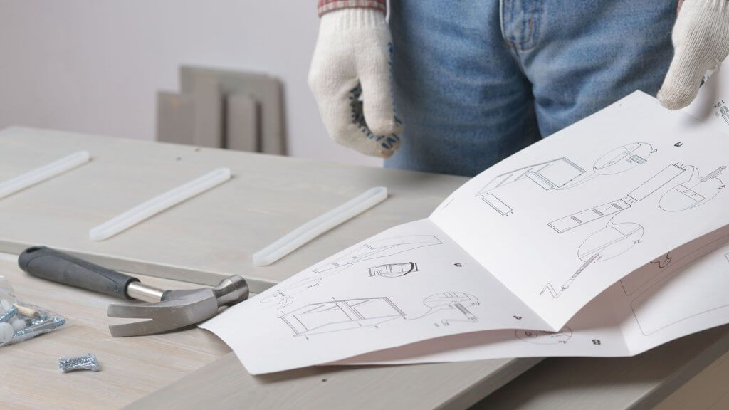 man looking at instructions for ikea product